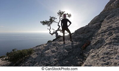 Young woman looks on the sun beams through branches of a pine on a mountain above Black sea in Crimea. Lady on the summit in beautiful scenery above the sea.
