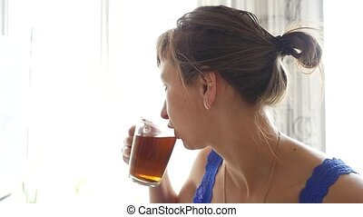 woman looks out the window and drinks her morning tea