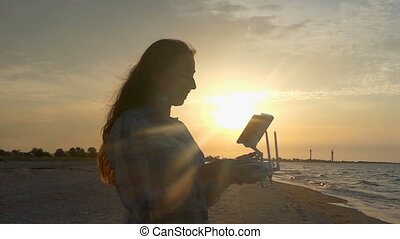 Young woman looks up with a flying drone panel at sunset in slo-mo