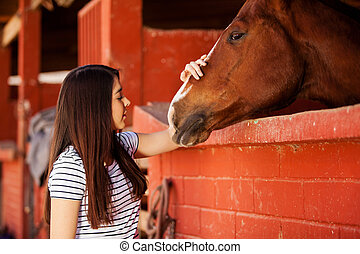 Young woman loving her horse
