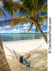 Young woman lying in a hammock on a tropical beach