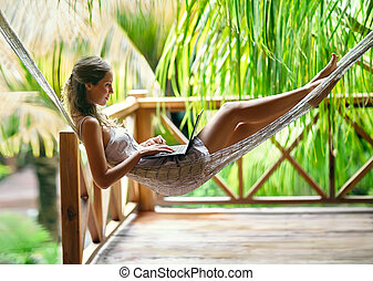Young woman lying in a hammock with laptop - Young beautiful...
