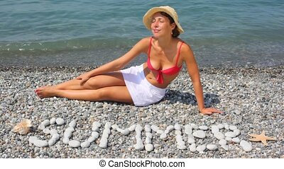 young woman lying in beach, SUMMER inscription in foreground