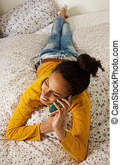 Young woman lying in bed and talking on cell phone