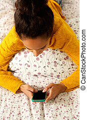 Young woman lying in bed looking at mobile phone