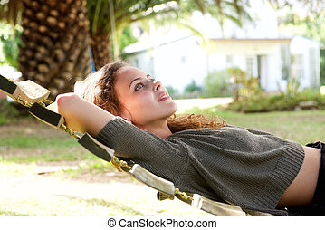 Young woman lying in hammock outside house