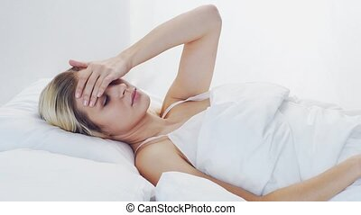 Young woman lying in the bed. Beautiful blond sleeping girl. Morning in the bedroom, daylight from the window. Health and rest concept.