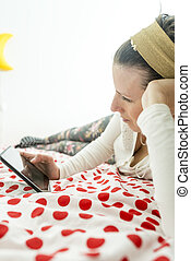 Young woman lying on a bedspread looking at her digital tablet