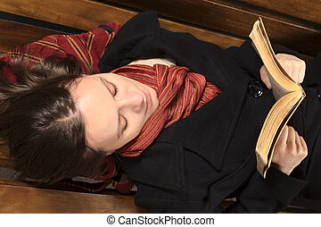 Young woman lying on a bench reading