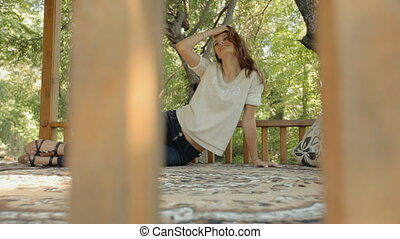 Young woman lying on a carpet in the gazebo in the woods