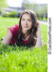 Young woman lying on a green lawn