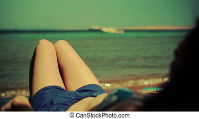 Young woman lying on beach of sea, wears sunglasses. Golden color grading