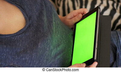 Young Woman Lying on Bed and using Tablet with Green Screen at Home.