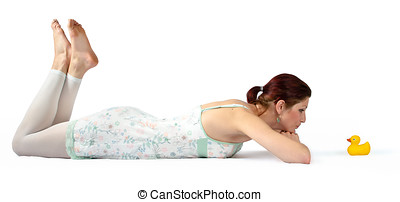 Young woman lying on floor looking at rubber duck