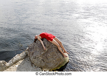 Young woman in red dress lying on rock at coast
