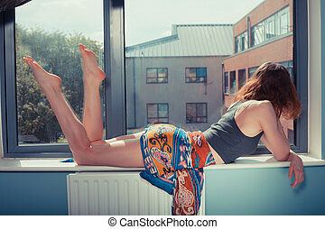 Young woman lying on window sill - Beautiful young woman...