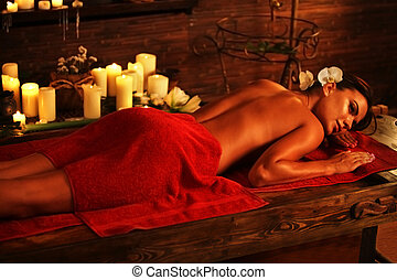 Young woman lying on wooden spa bed in massage spa salon.