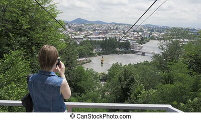 Young woman make photo of ropeway, Georgia, Kutaisi - Young...
