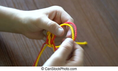 Young woman makes a bracelet from a multi-colored rope