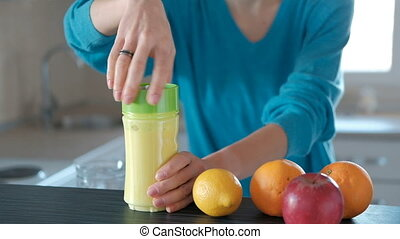 Young woman makes big glass of healthy fruits smoothie at home.
