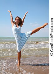 young woman makes exercise on the edge of the sea
