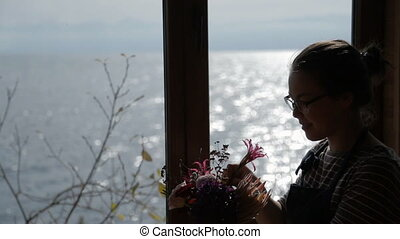 Young woman makes floral bouquet standing by window.