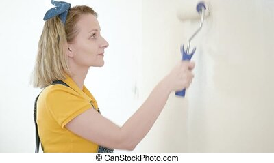 Young woman makes repairs - Young female makes repairs in...