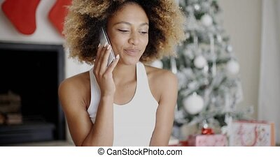 Young woman making a call at Christmas on her mobile phone...