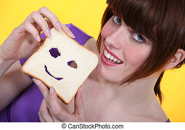 Young woman making a face in her slice of bread