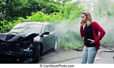 Young woman making a phone call after a car accident, smoke in the background.