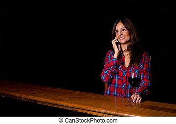 young woman making a phone call at the bar