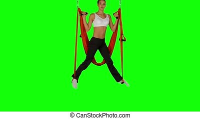 Young woman making antigravity yoga exercises with red hammock on a green screen