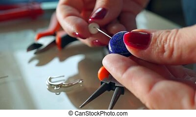 Young woman making earrings in her workshop. Close up shot