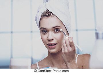 Young woman making eye makeup