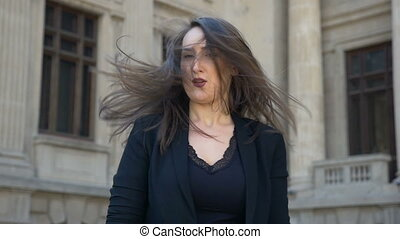 Young woman making face expression shaking her hair and turning from sadness to happiness in slow motion