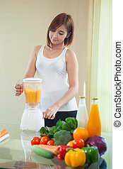Young Woman Making Fruit Smoothie in Blender