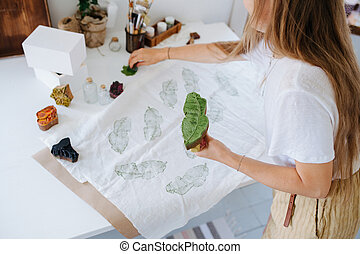 Young woman making green leaf-shaped prints on fabric with wooden stamp.