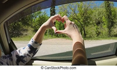 Young woman making heart from hands in car window at sunny...