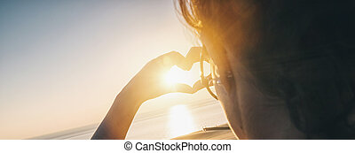 Young woman making heart with her hands at sunset on the ocean