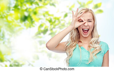 young woman making ok hand gesture - fun, emotions,...