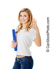 Young woman making ok sign holding binder