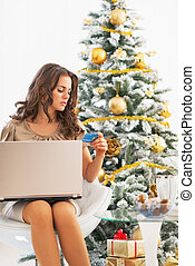 Young woman making online shopping near christmas tree