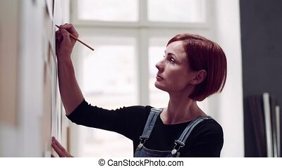 Young woman making plans for work indoors, writing on board...