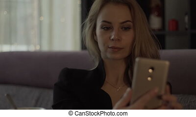 Young woman making selfie on mobile phone during business lunch in trendy cafe