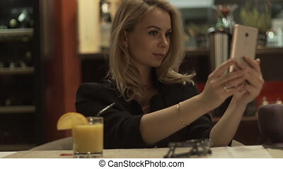 Young woman making selfie on mobile phone on background interior modern cafe