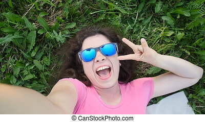 Young woman making selfie photo in park