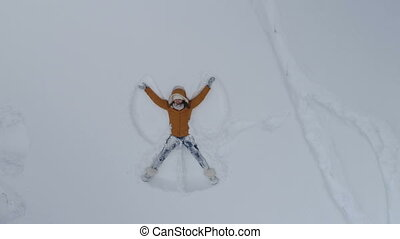 Young woman making snow angels, aerial
