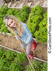 Young woman making use of a rake in her garden