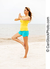 Young woman making yoga exercises on the beach