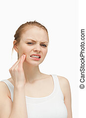 Young woman massaging her jaw against white background